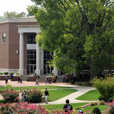 The front of Beaman Student Life Center with students walking in front on a sunny day